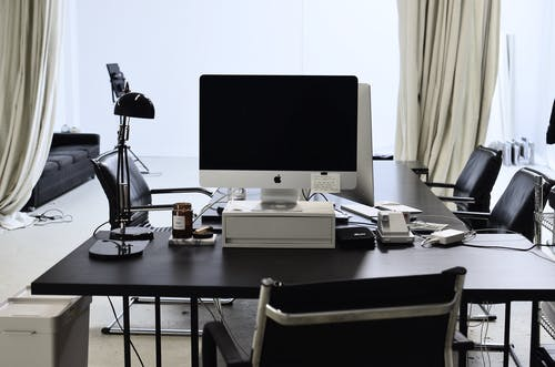 Interior of convenient workspace with contemporary computer placed on table with lamp in modern light office with couch against window