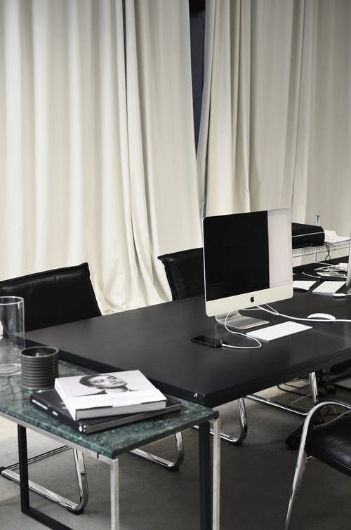 Black and white of contemporary computer placed on table in simple contemporary workplace of office