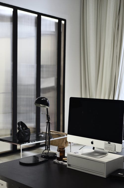 Interior of contemporary workplace of office with convenient computer and lamp on table
