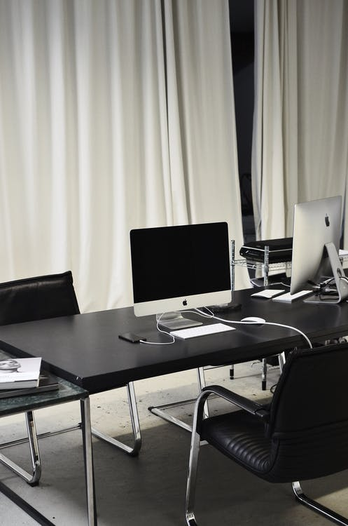 Black and white of computer with wireless keyboard and mouse placed on table near smartphone on charge in business office