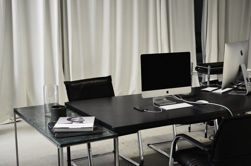 Black and white of workspace of office with computers placed on table with wireless mouse and keyboard near smartphone