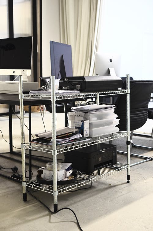 Iron shelves with hardware placed near table with computers in office in daytime