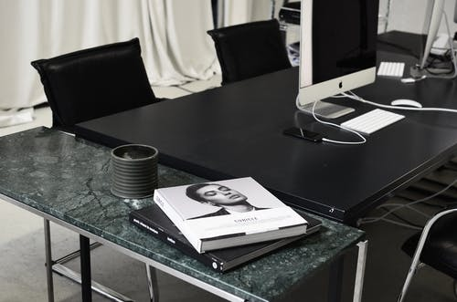 Modern computers and smartphone placed on black table near marble table with books in contemporary workspace