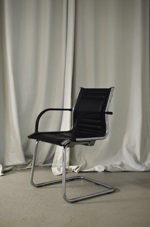 Black chair placed near light curtains