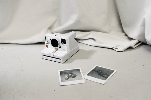 Instant photos placed near modern instant photo camera