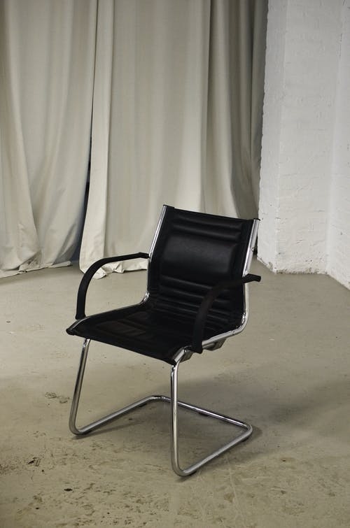 Black chair placed in room against curtains