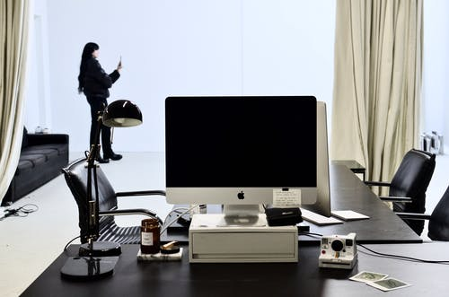Monitor of modern computer and instant photo camera placed on black table in modern workspace against female standing with smartphone near window with light curtains