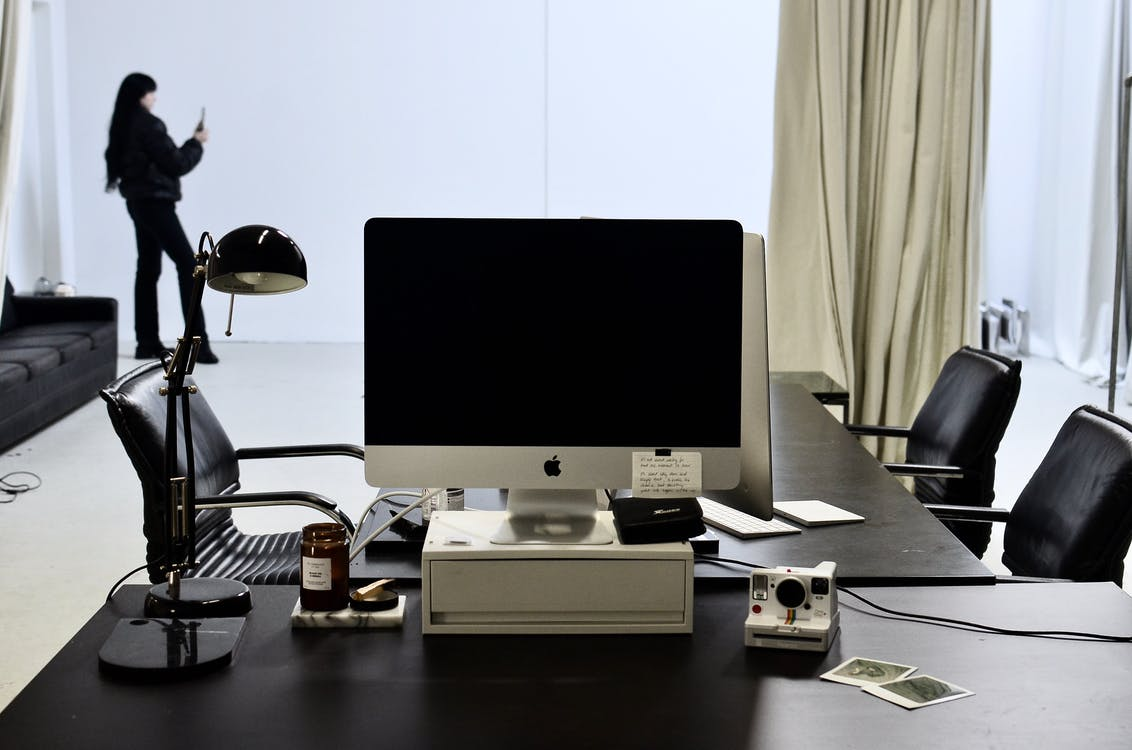 Contemporary computer placed on black table with instant photo camera and lamp against anonymous woman with long black hair in stylish clothes taking pictures on smartphone