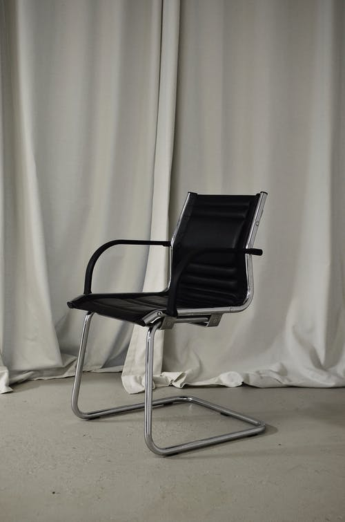 Black chair with leather seat and metal elements placed in light room against long curtain