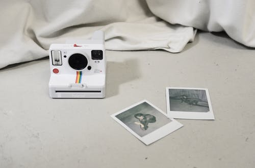 Modern instant photo camera and photos placed on floor