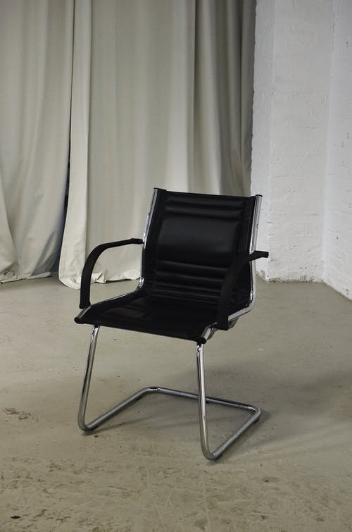 Comfortable office chair with black leather seat and metal elements placed in room with light brick wall and curtain