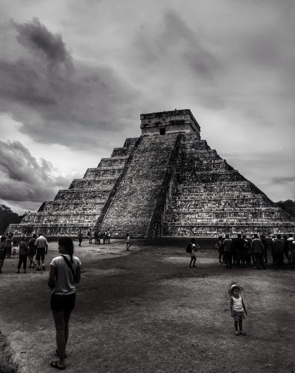 People Walking on Brown Sand Near Pyramid Under Gray Cloudy Sky