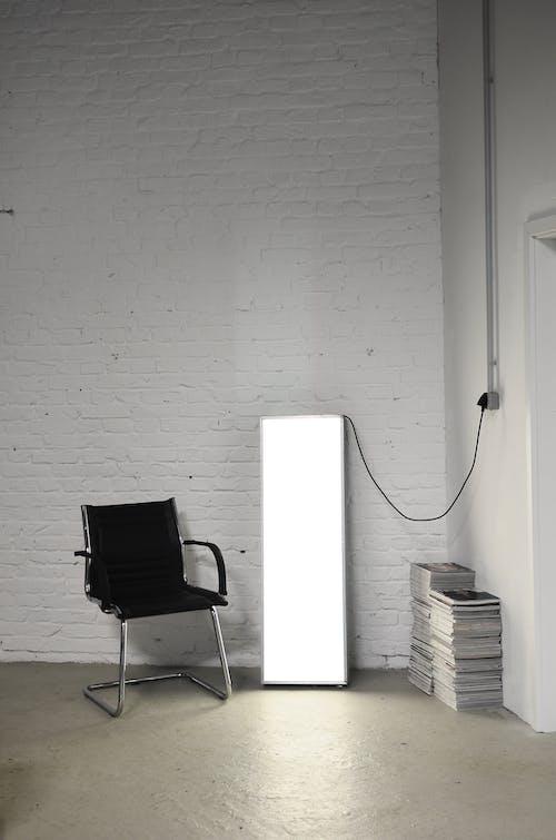 Armchair near floor lamp in empty house