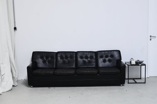 Black and white of leather couch near rectangular shaped table with decorative candle and vases in living room