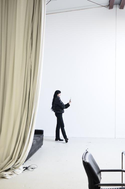 Man In Zwarte Jas En Zwarte Broek Staande Op Witte Vloertegels