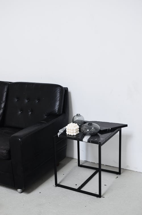 Black and white of living room interior with leather sofa near table with decorative candle and vases at home