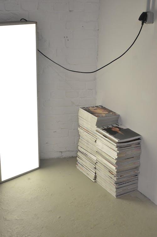 Stacked magazines on floor near photo studio lamp