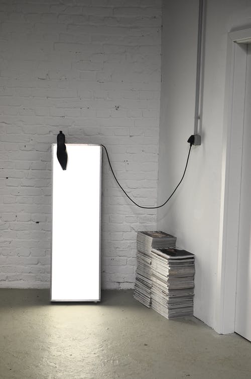Room corner with stacked magazines and lamp for photography
