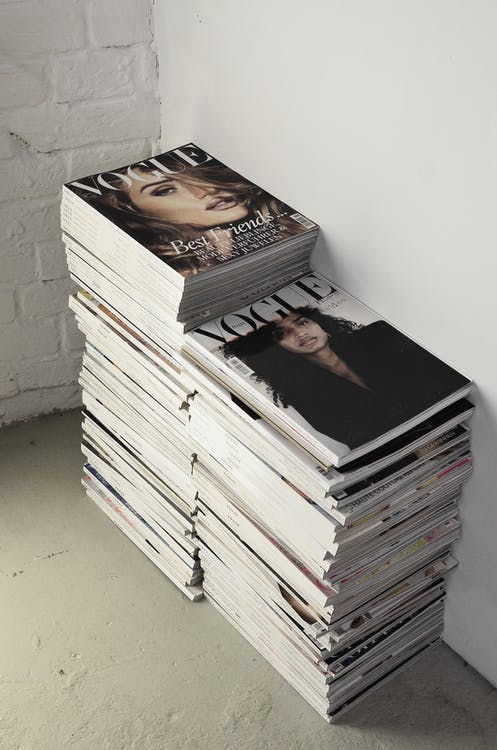 High angle many fashion magazines stacked on floor against white brick wall in studio