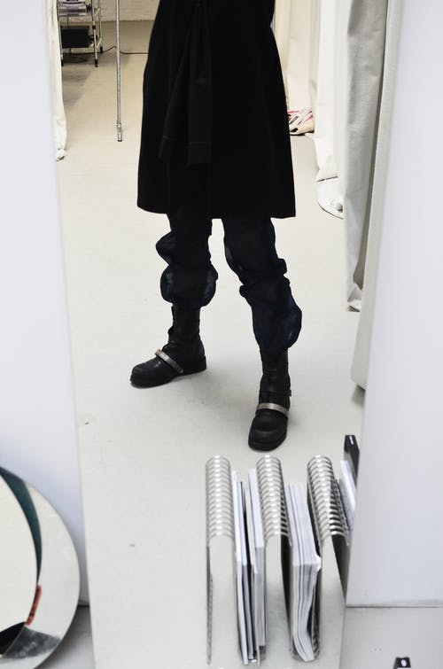 Crop anonymous person in loose trousers and black skirt reflecting in narrow mirror in light studio