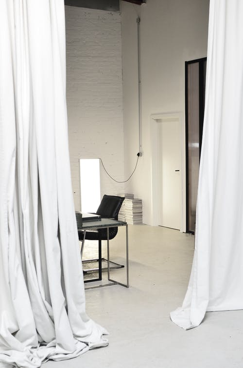 Interior of spacious loft studio with meeting table and chairs surrounded by hanging white curtains
