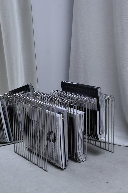 Collection of modern fashion magazines on metal rack placed on floor near mirror and curtain in room corner