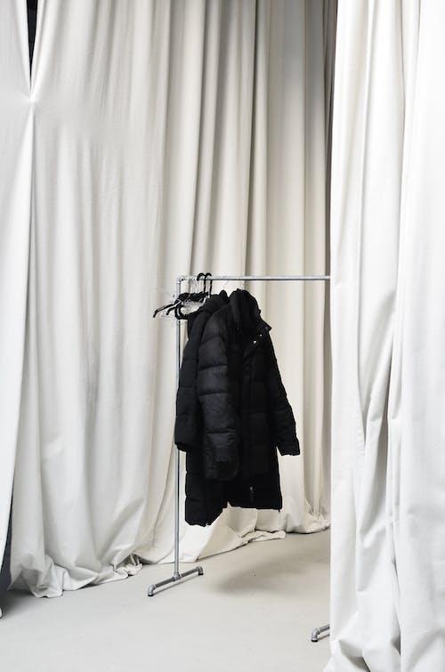 Abrigo Negro Colgando De Una Percha Negra