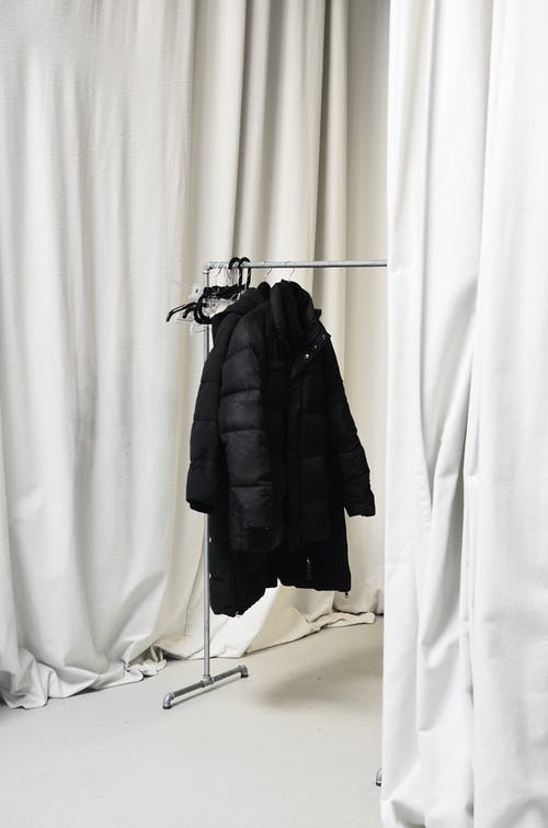 White curtains and stylish jackets on metal hanger in spacious room at home