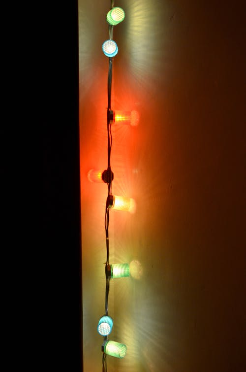 Multicolored Christmas lights with bright illumination on wall in dark room at night