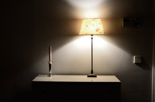 Interior of room in retro style with glowing lamp near candle in holder on shelf