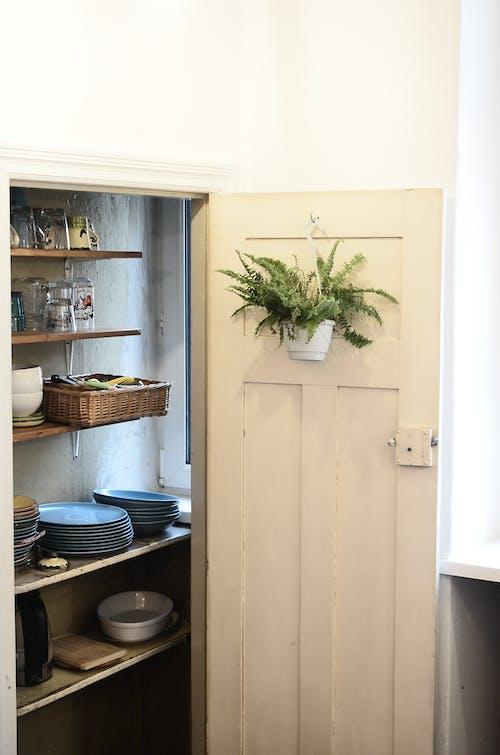 Stack of kitchenware on shelves behind door