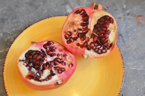 Ripe pomegranate on yellow plate