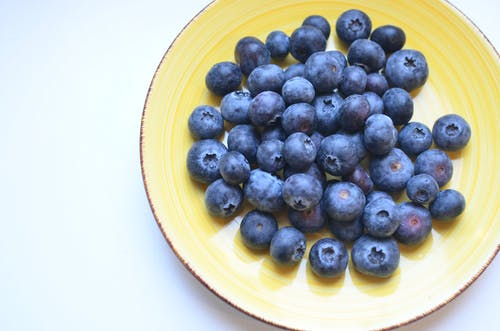 From above of ceramic plate with fresh appetizing berries on table in kitchen