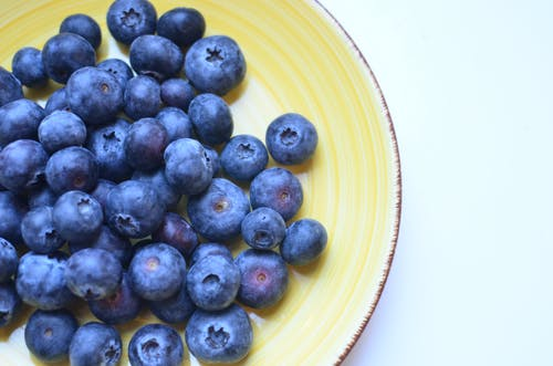 Top view of natural juicy blueberry with sweet taste on yellow ceramic plate