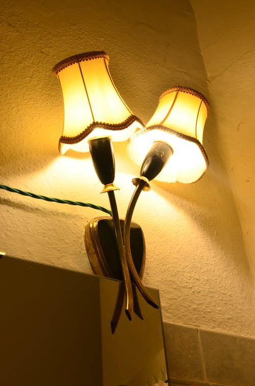 From below of sconce with bright shiny lamps hanging on rough wall with wire in dark room in evening time