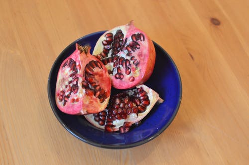 Fruta De Romã Fatiada Em Prato De Cerâmica Azul