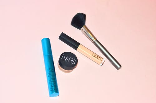 Top view of professional mascara concealer and cosmetic foundation placed near brush for applying makeup on pink background in studio