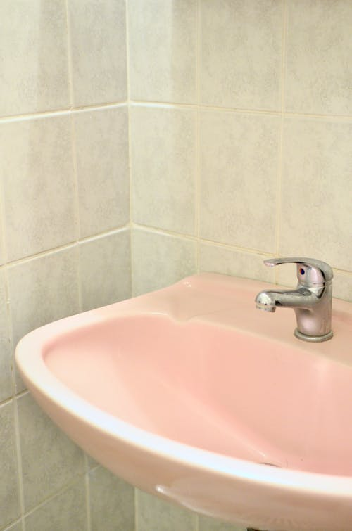Pink sink with faucet placed at corner of bathroom with tiled wall in room during daily hygiene routine in flat