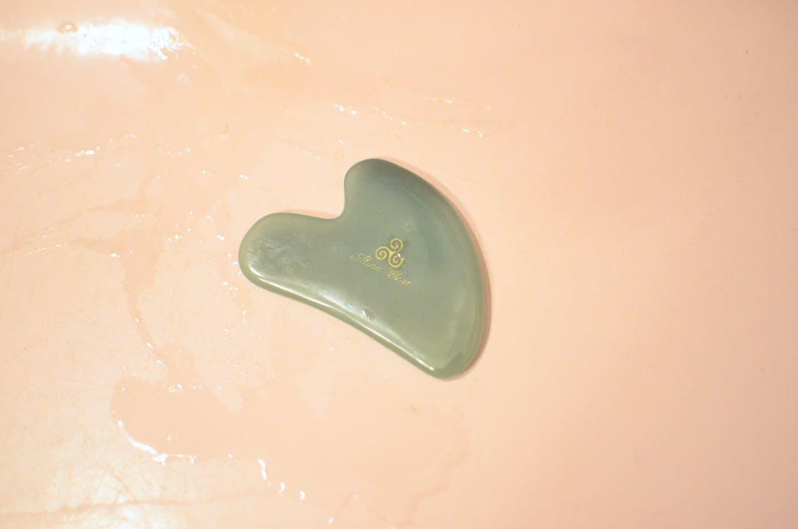 Jade Gua Sha tool in bathtub