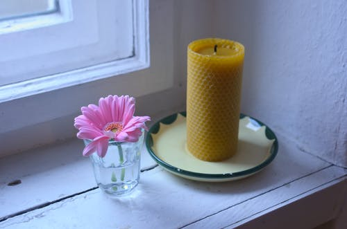 High angle of pink gerbera in glass and yellow candle on plate placed on wooden windowsill near white window in room