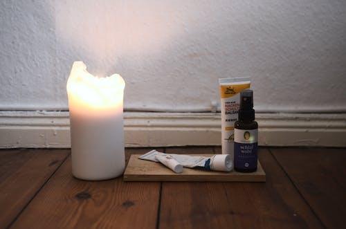 茶色の木製テーブルの上の白い柱のキャンドル
