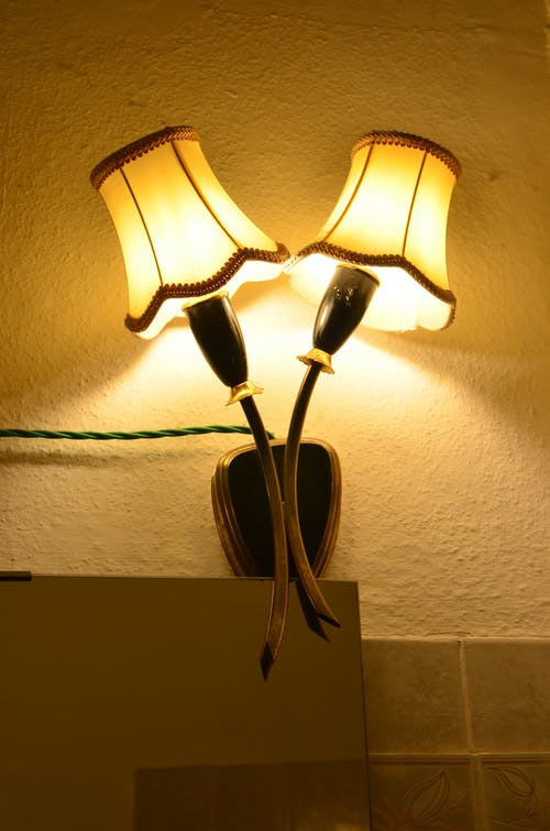 Glowing electrical bulbs hanging on shabby wall with wire in dark room with mirror and tile in flat at evening