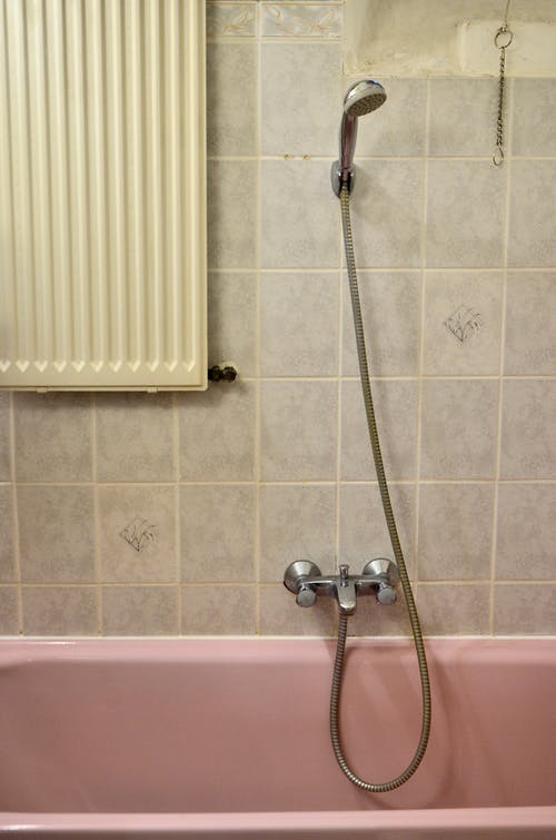 Stainless Steel Shower Head on White Ceramic Wall Tiles