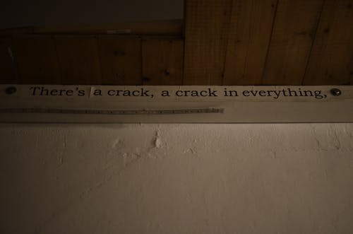 From below of phrase written on paper and nailed on white shabby wall near wooden ceiling in room in neglected house