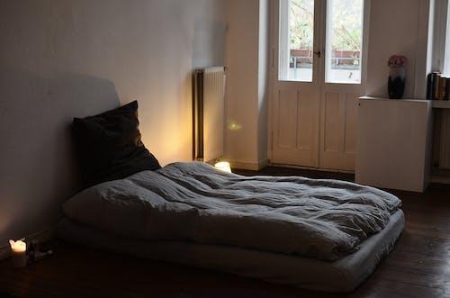 白色床头柜附近的白色床单