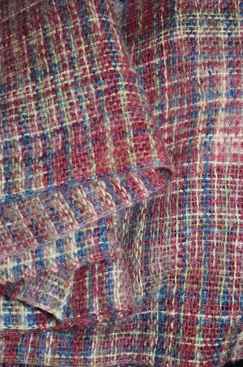 From above of knitted boucle fabric with checkered ornament for sewing warm apparel
