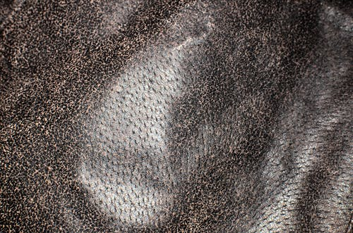 Full frame textured background of uneven natural leather fabric made of animal skin