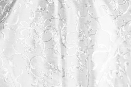 Background of white curtain with bright thick textile and creative design with ornamental elements creating swirls hanging in light room