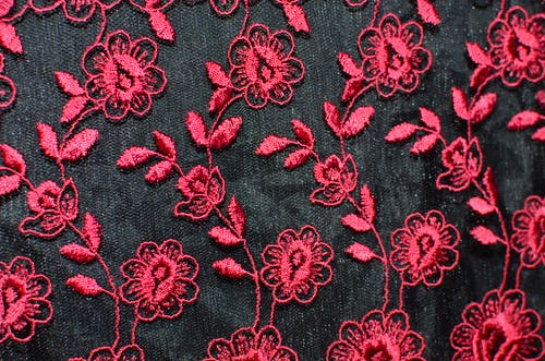 Seamless background of creative flowers with leaves embroidered on black fabric with red thread creating symmetrical pattern on thick textile