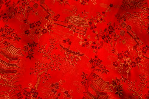 Background of bright fabric with oriental design of tree and floral pattern with traditional huts elements on thick decorated textile